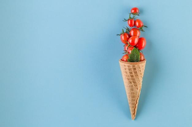 Tomates frescos saudáveis em cones de waffle em fundo azul
