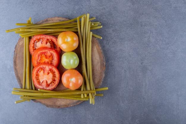 Tomates frescos, verdes e vermelhos na placa de madeira.