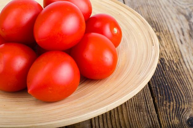 Tomates frescos vermelhos em fundo de madeira