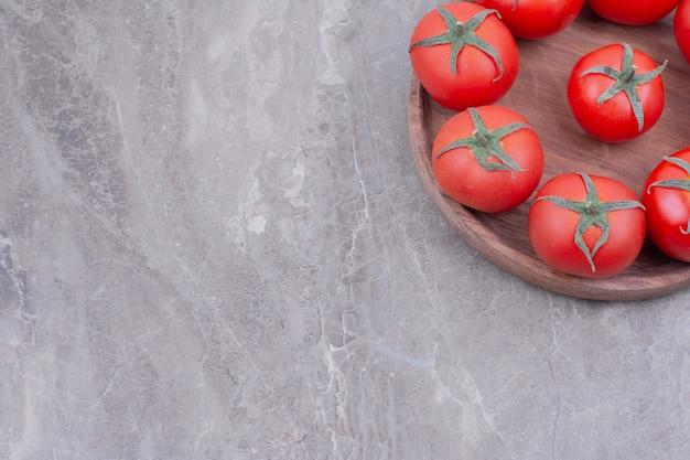 Tomates isolados em uma travessa de madeira sobre o mármore
