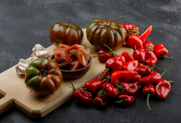 Tomates kumato com fatias, pimentão vermelho, bulbos de alho na parede cinza e tábua, vista de alto ângulo.