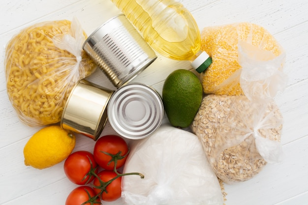 Tomates, latas, abacates e mais comida na mesa de madeira branca