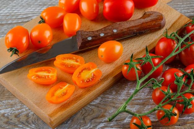 Tomates maduros com faca na placa de madeira e corte, vista de alto ângulo.