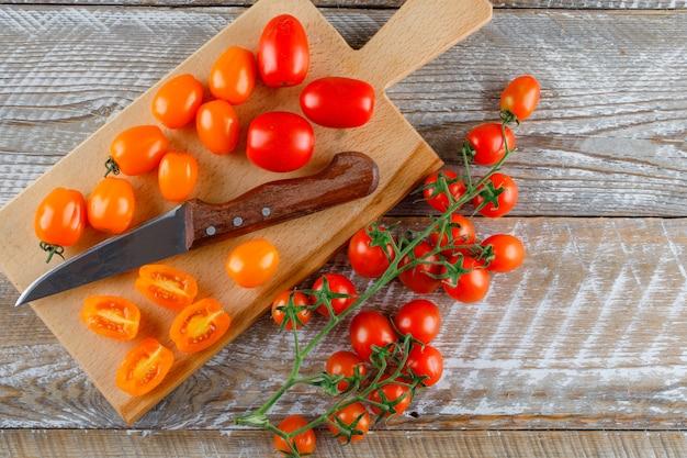 Tomates maduros com faca plana leigos na tábua de madeira e