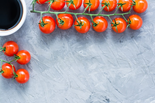 Tomates maduros de cereja mel em um ramo e molho balsâmico em uma tigela em cinza de concreto
