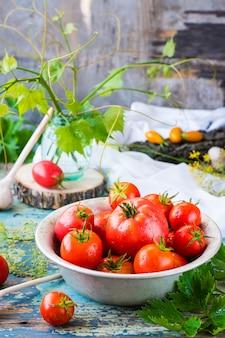 Tomates maduros em um prato sobre uma mesa de madeira