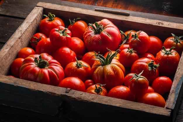 Tomates maduros em uma caixa de madeira legumes frescos em um fundo preto de madeira Foto Premium