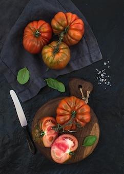 Tomates maduros frescos da herança e folhas da manjericão na placa de madeira rústica sobre a pedra preta.