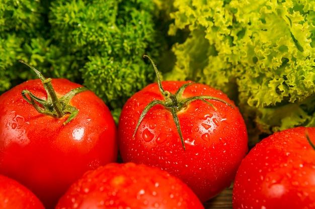 Tomates maduros frescos em uma mesa de madeira com uma salada verde