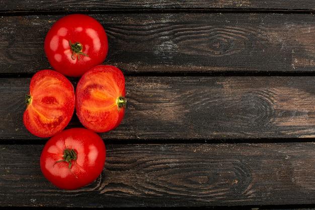 Tomates maduros frescos vermelhos alinhados em uma mesa de madeira
