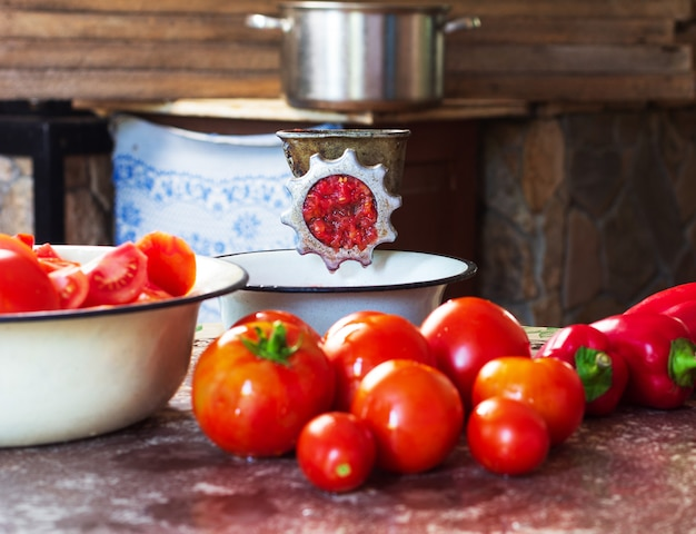 Tomates maduros, pimentos vermelhos e um moedor de carne vintage artesanal em cima da mesa na cozinha da aldeia