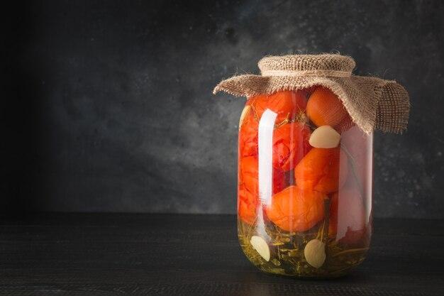 Tomates marinados caseiros legumes enlatados em potes de vidro na placa de madeira