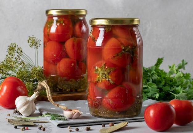 Tomates marinados com coentro em potes para o inverno em fundo cinza