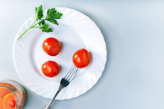 Tomates marinados picantes suculentos com salsa em um prato branco.