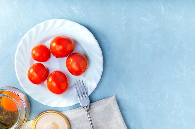 Tomates marinados picantes suculentos em um prato branco na superfície azul.