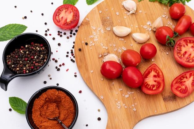 Tomates na tábua com conceito de vista superior de especiarias na superfície branca