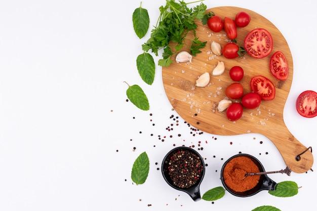 Tomates na tábua de madeira com vista superior de especiarias na superfície branca