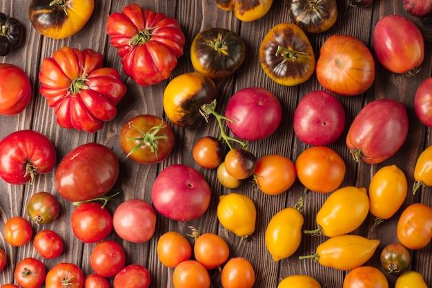 Tomates orgânicos saudáveis em um fundo de madeira. tomates variados em fundo de madeira rústico. tomate vermelho na mesa