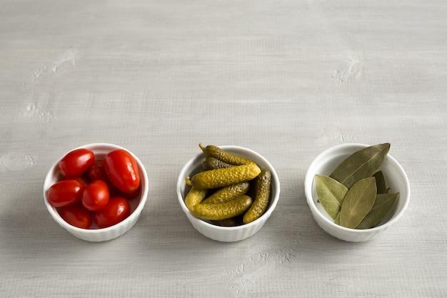 Tomates, pepinos e folhas de louro em conserva, fermentados em tigelas brancas vista superior sobre um fundo claro de madeira com lugar para texto.