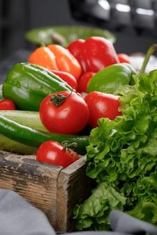Tomates, pepinos, hortaliças em uma bandeja de madeira.