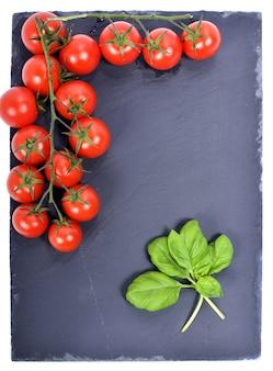 Tomates pequenos apresentados em uma placa de ardósia