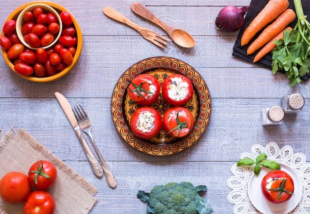 Tomates recheados com queijo e vegetais diferentes na madeira