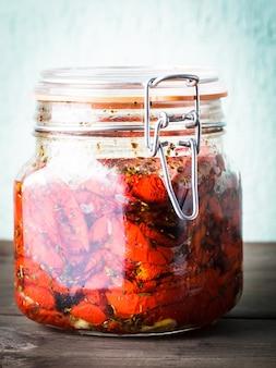 Tomates secos ao sol com ervas e azeite em uma jarra