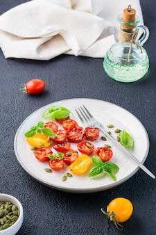 Tomates secos ao sol com manjericão, sementes de gergelim e abóbora em um prato em um fundo preto. comida vegetariana. visão vertical