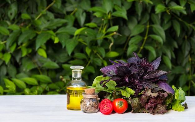 Tomates suculentos, azeite e verduras para salada
