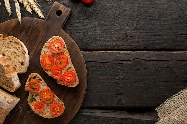 Tomates torradas e pão em uma placa na madeira