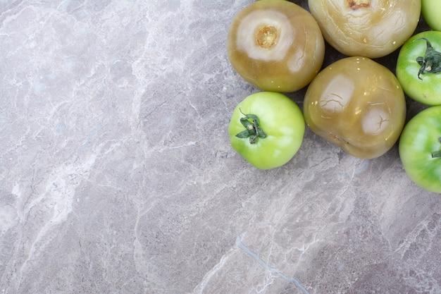 Tomates verdes frescos e tomates em conserva na superfície de mármore.