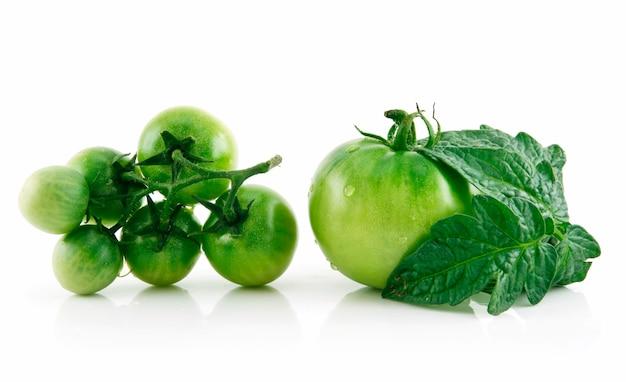 Tomates verdes molhados maduros com folhas isoladas no fundo branco