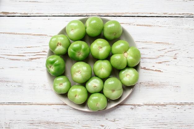 Tomates verdes, picles na mesa de madeira branca com verde e vermelho e pimenta, erva-doce, sal, pimenta preta, alho, ervilha, close-up, conceito saudável, vista superior, configuração plana