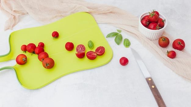 Tomates vermelhos com manjericão na placa de desbastamento com faca e lenço no contexto branco