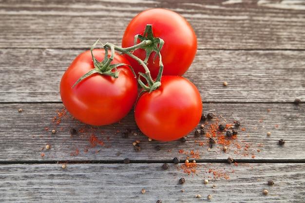Tomates vermelhos com pimenta em uma velha mesa de madeira
