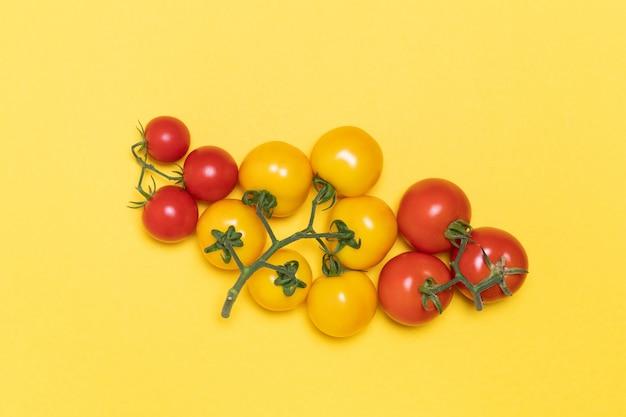 Tomates vermelhos e amarelos no isolado em fundo amarelo, criativo