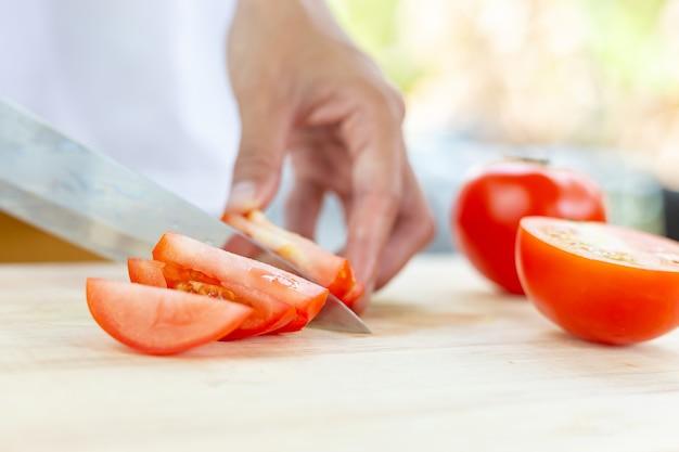 Tomates vermelhos e fatias na tábua de madeira