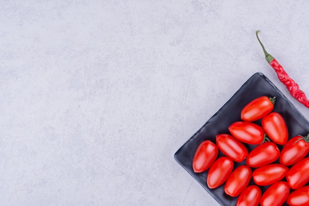 Tomates vermelhos e pimenta malagueta na superfície cinza