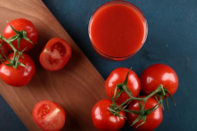 Tomates vermelhos e um copo de suco em uma placa de madeira. vista do topo.