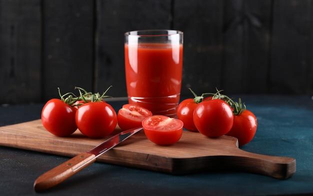 Tomates vermelhos e um copo de suco em uma placa de madeira.