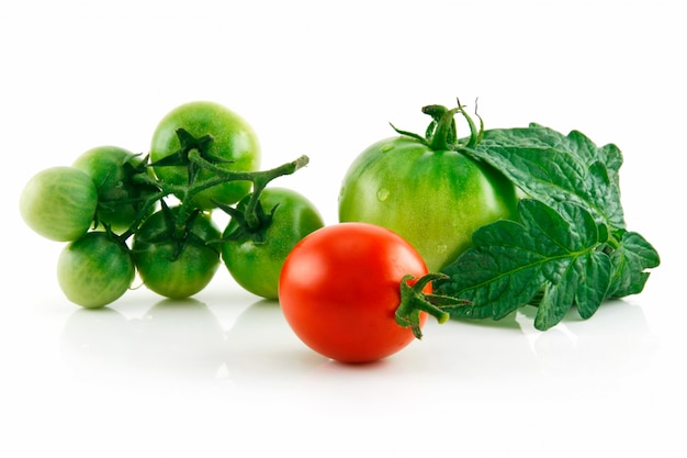 Tomates vermelhos e verdes molhados maduros com as folhas isoladas no fundo branco