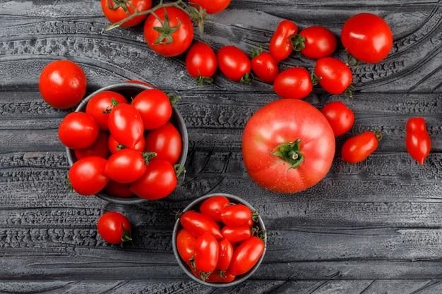 Tomates vermelhos em mini baldes na parede de madeira cinza, vista superior.