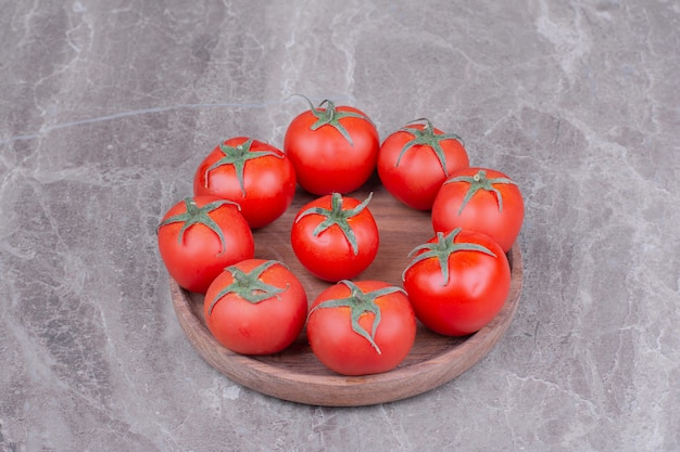 Tomates vermelhos em uma travessa de madeira no mármore
