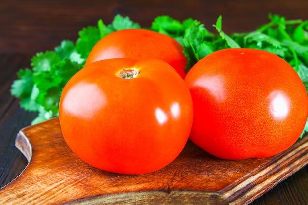 Tomates vermelhos frescos com coentro em uma mesa de madeira.
