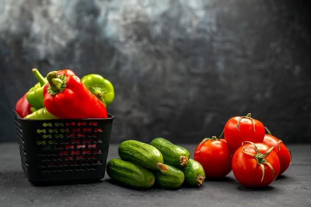 Tomates vermelhos frescos com pepinos em um fundo escuro foto colorida de refeição madura de vista frontal