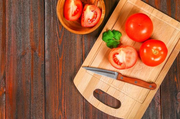 Tomates vermelhos frescos e metades cortadas com coentro em uma mesa de madeira. vista do topo.