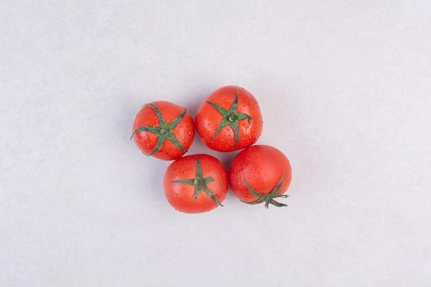 Tomates vermelhos frescos em branco.