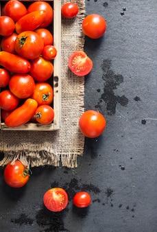 Tomates vermelhos frescos em caixa de madeira em fundo preto. camada plana, vista superior