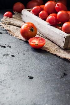 Tomates vermelhos frescos em caixa de madeira em fundo preto. copie o espaço
