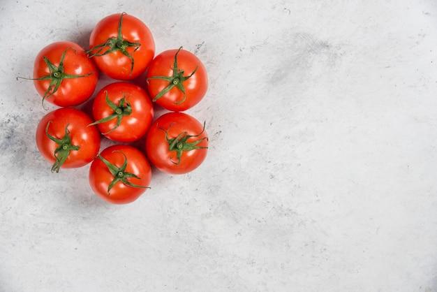 Tomates vermelhos frescos em um fundo de mármore